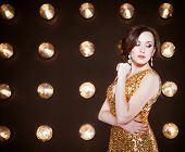 foto of superstars  - Superstar woman wearing golden shining dress posing - JPG