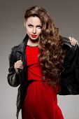 stock photo of jacket  - Beautiful young woman model brunette with long curled hair with red lips in leather jacket - JPG