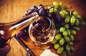 stock photo of brie cheese  - Brandy pours into a glass, grapes and brie cheese with a knife on the board