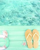 picture of beside  - Female flip flops on wooden platform beside sea - JPG