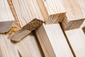 stock photo of lumber  - Wooden beams and planks. Lumber stacked at construction site ** Note: Shallow depth of field - JPG