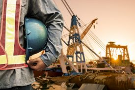 pic of check  - construction worker checking location site with crane on the background  - JPG