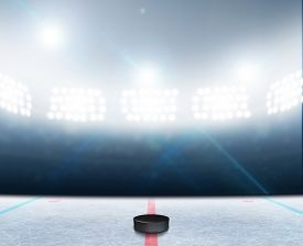 foto of illuminated  - A generic ice hockey ice rink stadium with a frozen surface and a hockey puck under illuminated floodlights - JPG