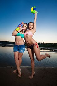 pic of pistols  - Two young girl posing with water pistols - JPG