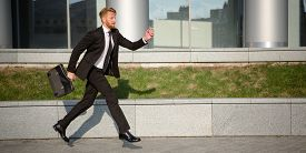 stock photo of running-late  - Handsome businessman running with brief case in hand - JPG