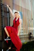 picture of boxcar  - Teen beauty in formalwear and sneakers holding on to the outside of a rusty old boxcar - JPG