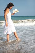 stock photo of beach hat  - Romantic scene of a book holding woman walking the coastline - JPG