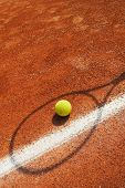 Tennis Concept - tennis ball near line with racket shadow over