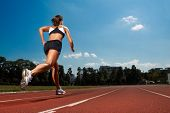 Athletic woman running on track