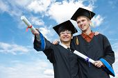 image of risen  - two excited graduate students in gown with risen hands holding diploma over blue sky - JPG