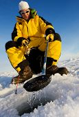 stock photo of ice fishing  - Ice fisherman cleaning ice from the hole with a ladle - JPG