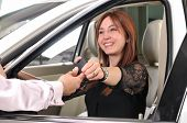 Car dealer giving keys of a new car to happy red head customer - a series of BUYING A NEW CAR images