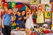 Small students with teacher finger painting in art school class. Teacher cheers children in kinderga poster
