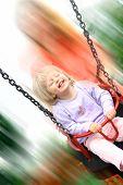 Kleinkind Mädchen genießen eine schnelle Fahrt auf Schaukel