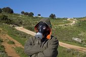 man with a gas mask and coat in landscape with winding path