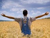farmer standing in a wheat field with his arms spread out