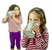 zwei Mädchen reden auf einem Blech Telefon, isoliert auf weiss
