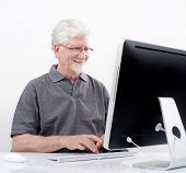 Alter Mann mit Computer zu Hause