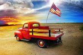 Red vintage pick up truck with American flag in wide open country side with dramatic sunset cloudscape