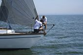 Two sportsmen - seamen put a sail on a wind. The yacht will go faster and the victory will be!