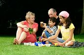 stock photo of priceless  - Young children spending precious time with their grandparents in the garden - JPG