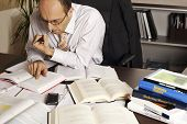 Businessman sitting at desk in office being busy studying books and papers.