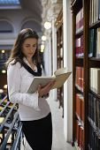 Young attractive student standing at bookshelf in old university library reading a book.