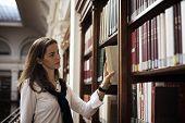 Muito aluna de pé na estante na biblioteca da Universidade velha à procura de um livro.