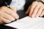 image of contract  - Businessman sitting at office desk signing a contract with shallow focus on signature - JPG