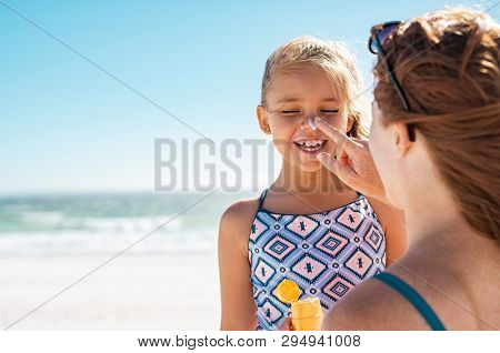 poster of Young mother applying protective sunscreen on daughter nose at beach. Woman hand putting sun lotion