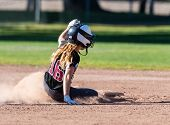 Female Teenage Softball Player In Black Uniform Sliding Safely Into Second Base. poster