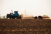 Tractor Preparing Land For Sowing. Farmer In Tractor Preparing Land With Seedbed Cultivator poster