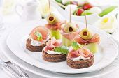 Canapes with ham and green pickled olives