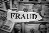 Fraud Concept. Torn Piece Of Paper With The Word fraud On Dollar Bills. Motion Blur. Black And Whi poster