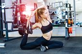 Flexible Slim Athletic Girl In Sportswear Stretching Her Muscular Body In The Sports Center. Active  poster