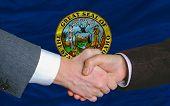 Delante de la bandera del Estado americano de Idaho dos empresarios apretón de manos después de mucho