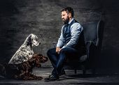 Bearded Hunter Wearing Elegant Clothes Sitting On A Sofa With His Two Purebred Setter Dogs. Studio P poster