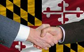 In Front Of American State Flag Of Maryland Two Businessmen Handshake After Good Deal