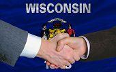 Delante de la bandera del Estado americano de Wisconsin apretón de manos de dos hombres de negocios después de mucho