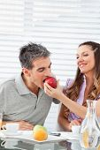 Married happy couple eating breakfast together with apples