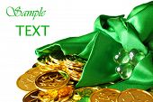 St. Patrick's day image of shiny gold shamrock coins spilling from a green satin bag with glass sham