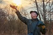 Man Launching A Drone Against The Rising Sun. Man Holds Drone On Arm Outstretched poster