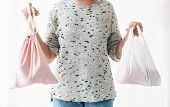Ban Single Use Plastic. Zero Waste Shopping Concept. Woman Holding In One Hand Groceries In Reusable poster