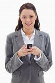 Close-up of a businesswoman smiling and holding her mobile against white background