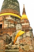Beautiful Bhudda Image In Front Of The Main Stupa (chedi) Of Wat Yai Chai Mongkhon Temple, Ayutthaya poster