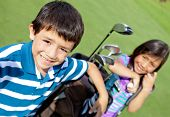 stock photo of golf  - Kids playing golf and holding a bag at the course - JPG