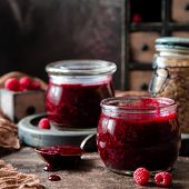 Two Glass Jars With Homemade Dark Red Jam Or Jelly Standing On Brown Concrete Table With Raspberries poster