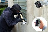 Surveillance Camera Capture And Record Caught Masked Thief With Hammer And Hand Holding Mobile Phone poster