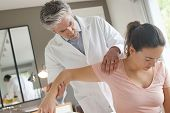 Physiotherapist helping patient with shoulder injury poster