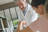 Physiotherapist working with patients wrist injury poster
